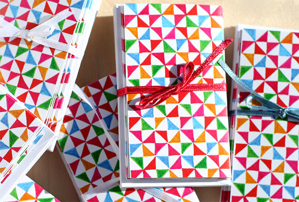Five Patch Design Hand Illustrated Colorful Pinwheels Mini Greeting Card Sets Shown Piled on a Table
