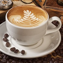 A barista produced cup of coffee with coffee beans