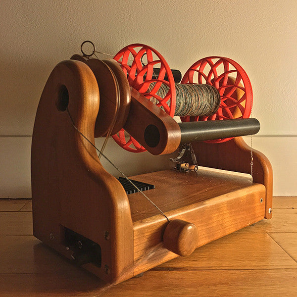 Flat-Pack Bobbin with Lotus whorls in Red, shown on wheel