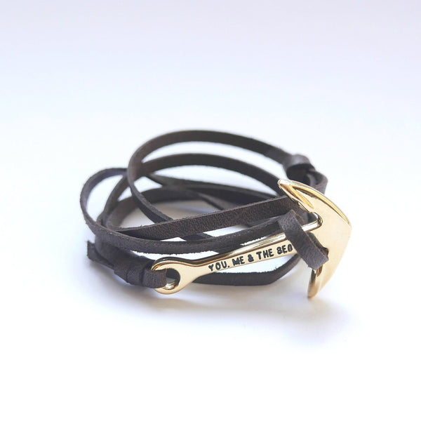 Nautical leather bracelet with a gold anchor and the band in brown.