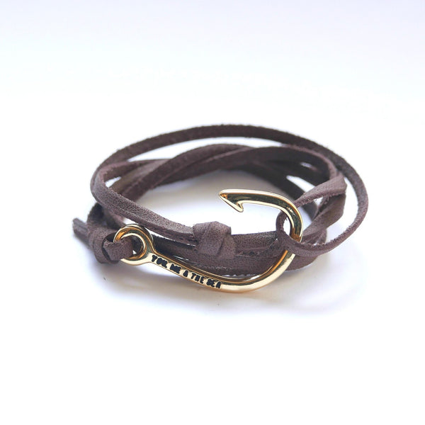 Nautical leather bracelet with a gold hook and the band in brown.