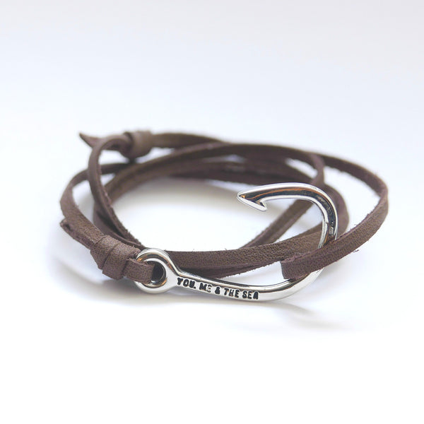 Nautical leather bracelet with a silver hook and the band in brown.
