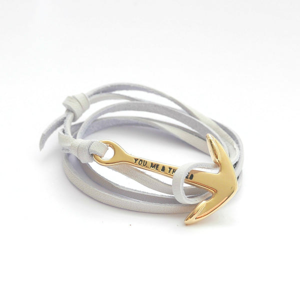 Nautical leather bracelet with a gold anchor and the band in white.