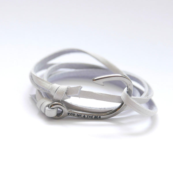 Nautical leather bracelet with a black hook and the band in white.