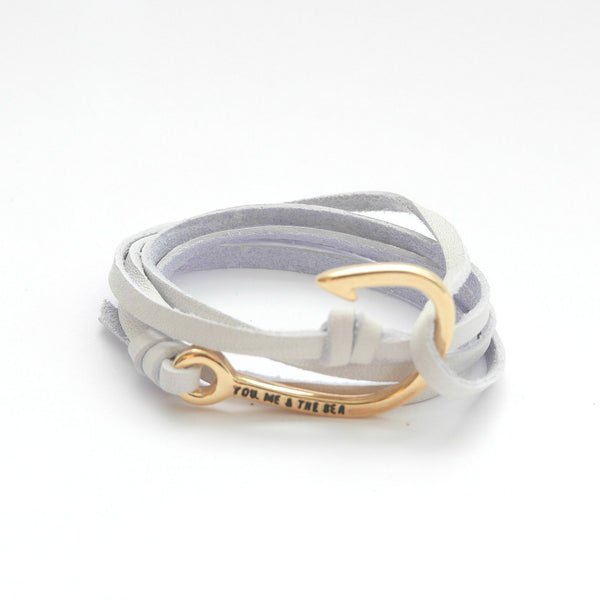 Nautical leather bracelet with a gold hook and the band in white.