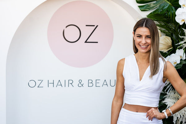 Girl standing in front of Oz Hair sign at rooftop event, displaying 2020 hair & beauty trends.