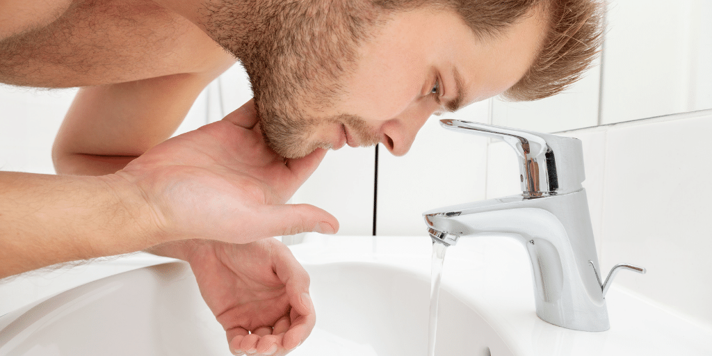Man Washing His Face With Cold Water