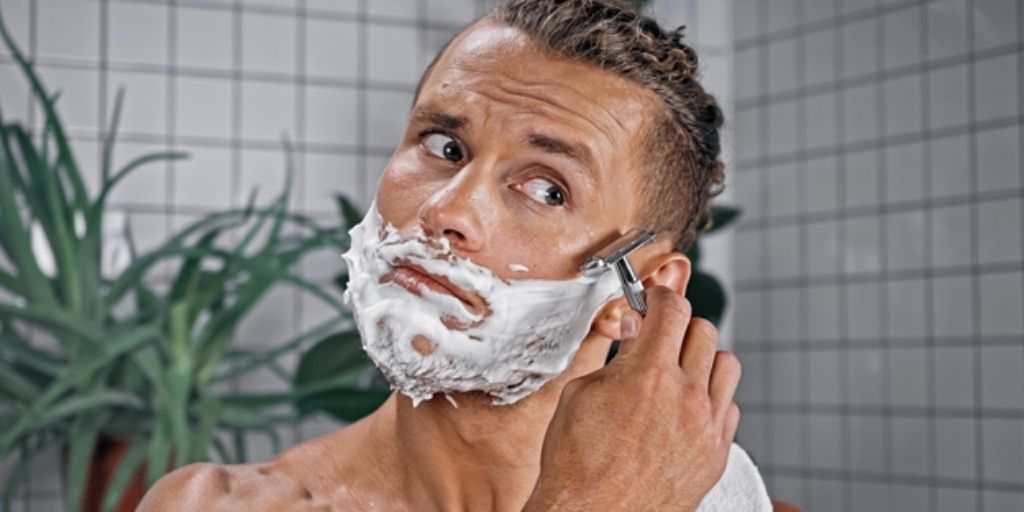 Man with shaving cream on his face using a safety razor