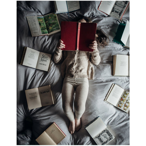 Child reading books laying on the bed