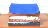 [Electric Blue Suede/Saddle Tan] Pommel Clutch front view sitting on stack of books