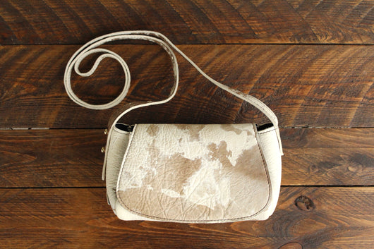 Cowhide Crossbody Saddle Bag front view features a unique pattern of shades of cream, khaki, and chocolate. Shown in color [Cowhide B].