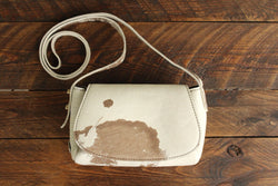 Cowhide Crossbody Saddle Bag front view features a unique pattern of shades of cream, khaki, and chocolate. Shown in color [Cowhide E].