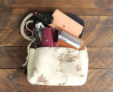 Cowhide crossbody shown with personal items in it.