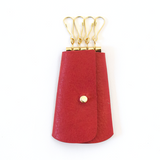 [Rouge Red] Vintage-inspired leather key pouch in [Crimson Red] with 4 gold key hooks and button stud closure. Fits standard-sized keys inside key pouch.