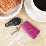Fuchsia George Key Case on table next to coffee mug and croissant.