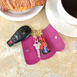 Fuchsia George Key Case open on table showing key and store loyalty cards inside.