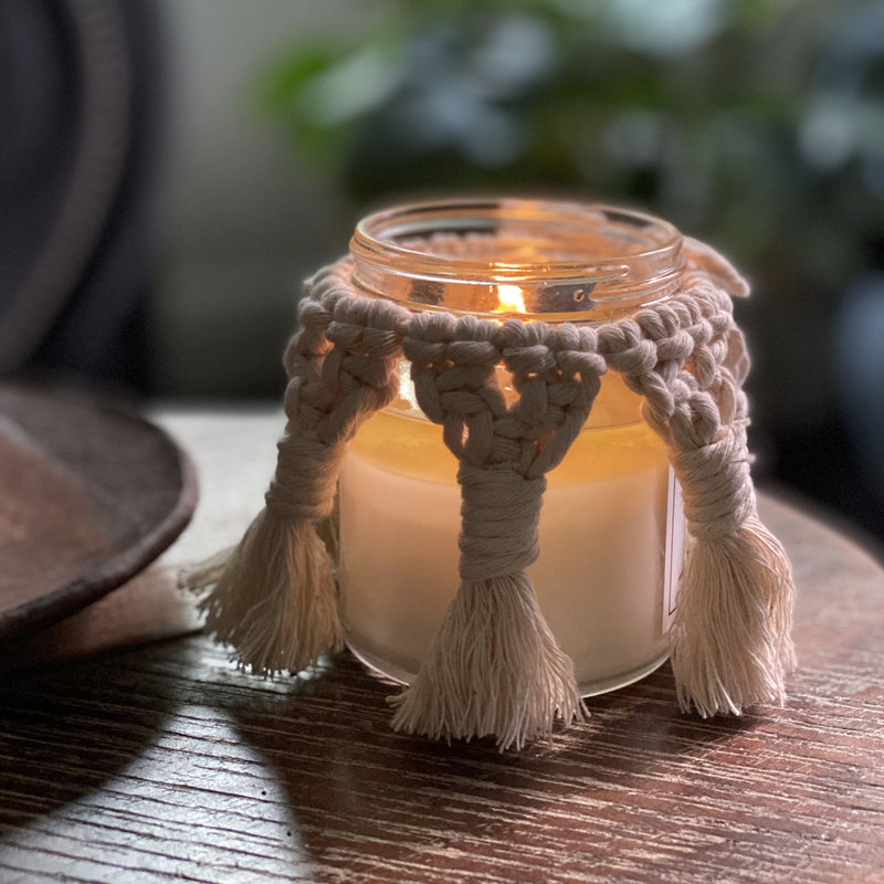 A Macrame candle cover.  It's off-white and braided.  Slightly darker than the candles when the candle's lit, but when the candle's unlit, the color looks lighter..