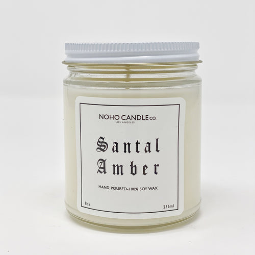 A 9-oz glass jar containing 8 ounces of white Santal Amber candle.  The lid is white and screws on.