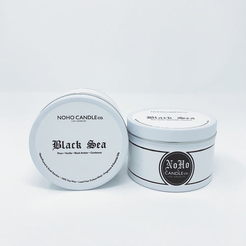 Two small travel tins of black sea candle