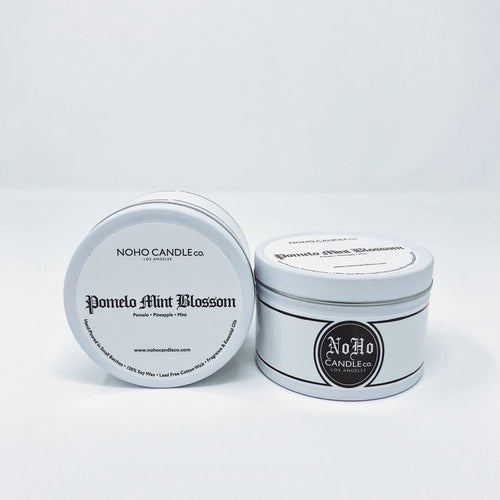 Two white tins of Pomelo Mint Blossom candles.  The color scheme on the tin is black and white with a vintage Chicano aesthetic.