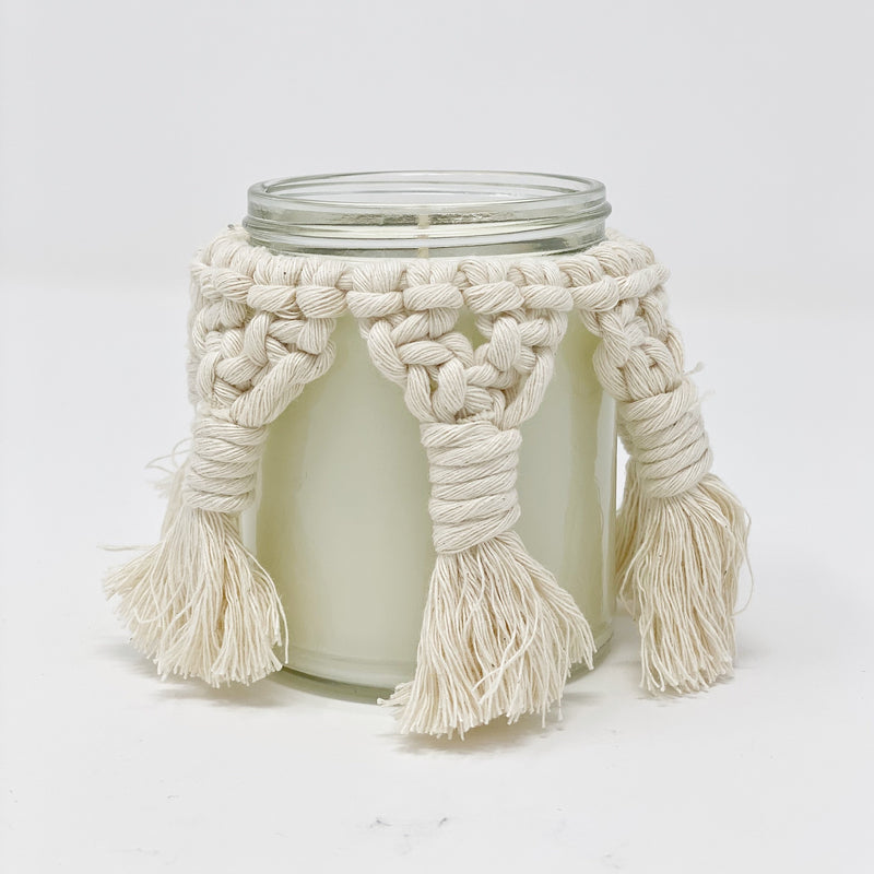 Unlit candle jar with a macrame cover.