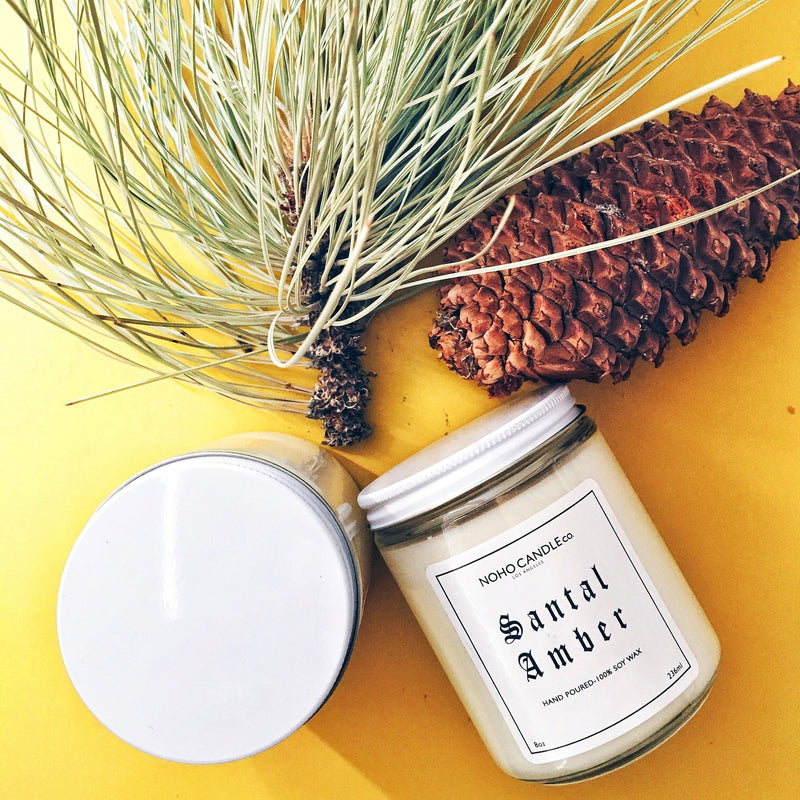 Two Santal Amber candle jars, one upright, and one on its side, next to a pinecone and pine needles for artistic flair.