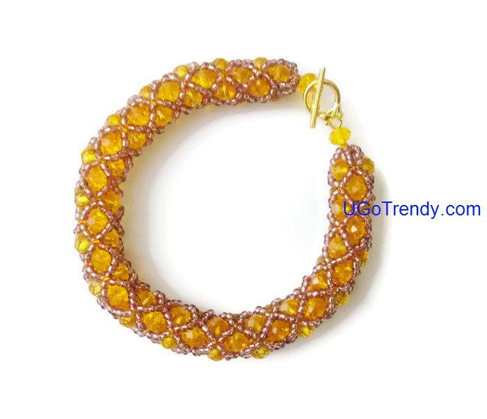Handwoven bracelet using gold coloured glass crystals and tiny beads