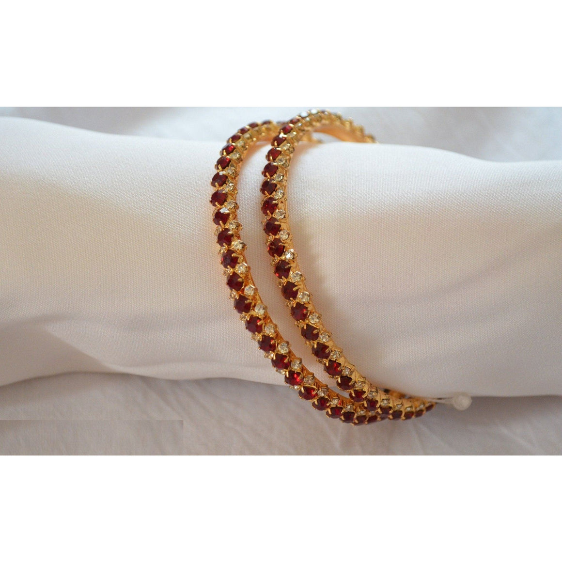 Set of 2 bangles with dark red cubic zirconia crystals with white crystals at the borders