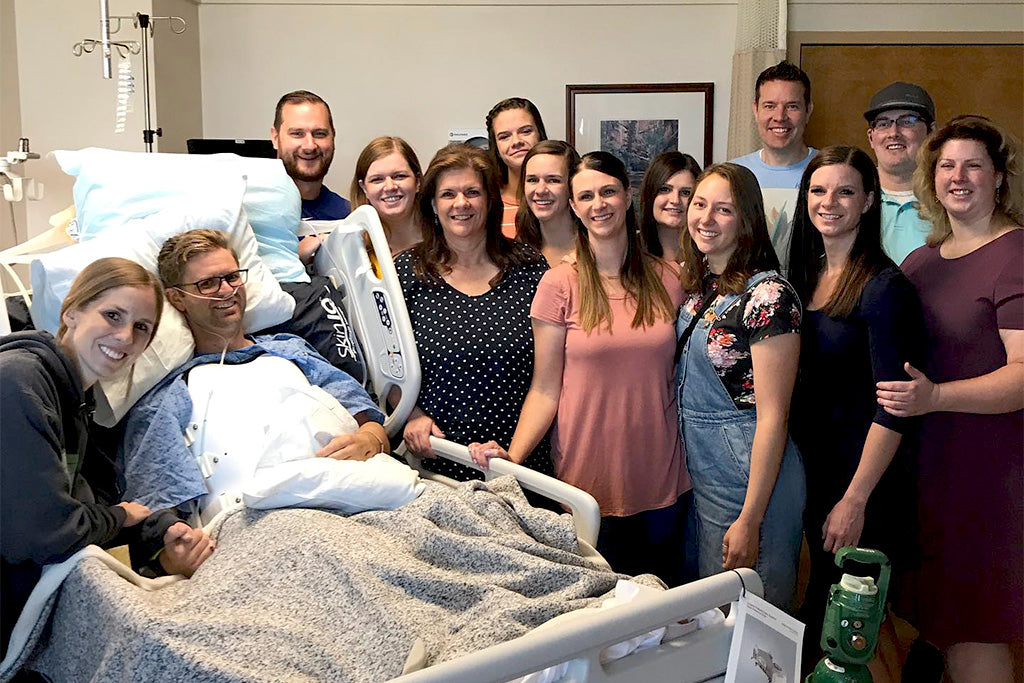 Austin Patten in hospoital bed surrounded by wife Jill and large group of friends.