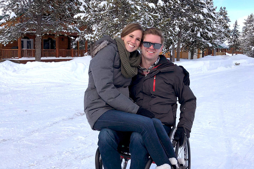 Jill Patten sitting in Austins lap as he sits in a wheelchair in a winter snowy setting.