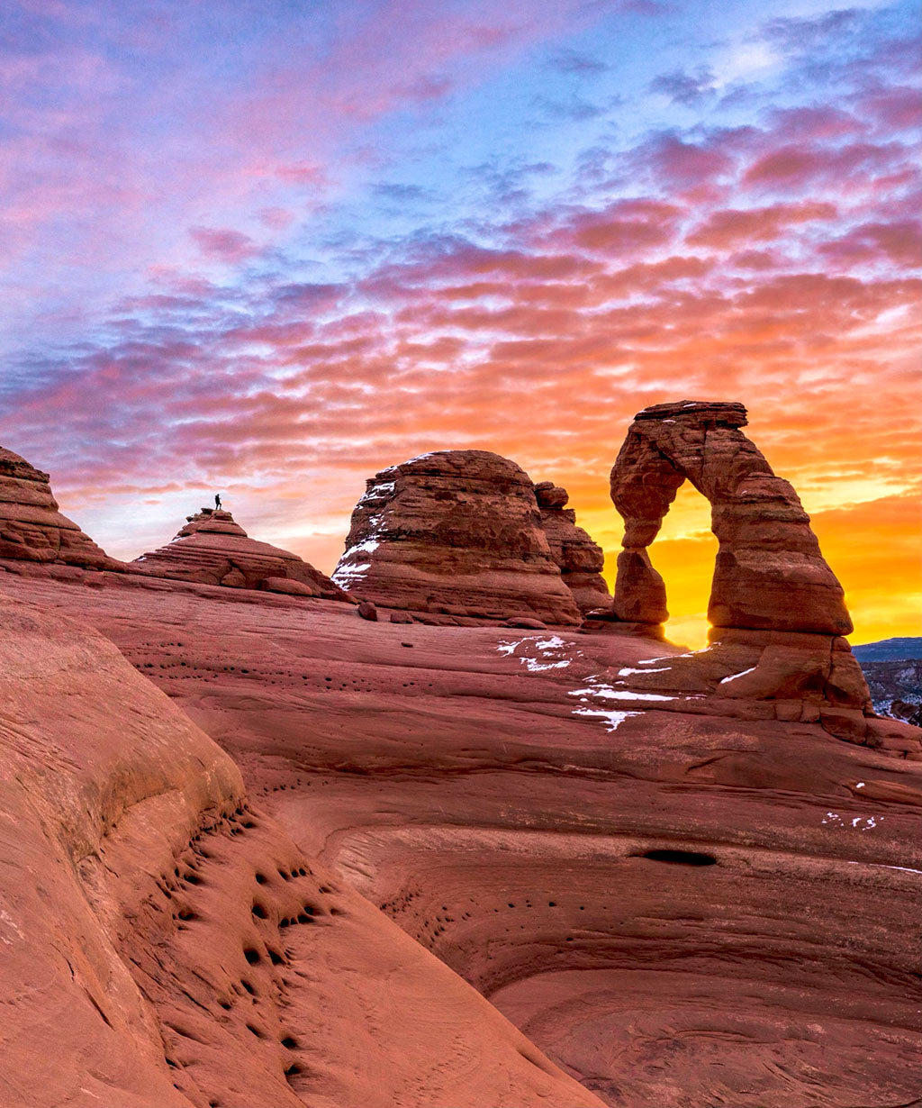 Delicate Arch in Arches National Park with a colorful sunset in the background