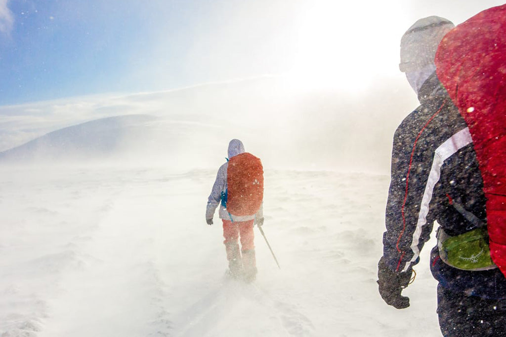 Two backpackers hiking through a wind-swept, snow-covered area in winter