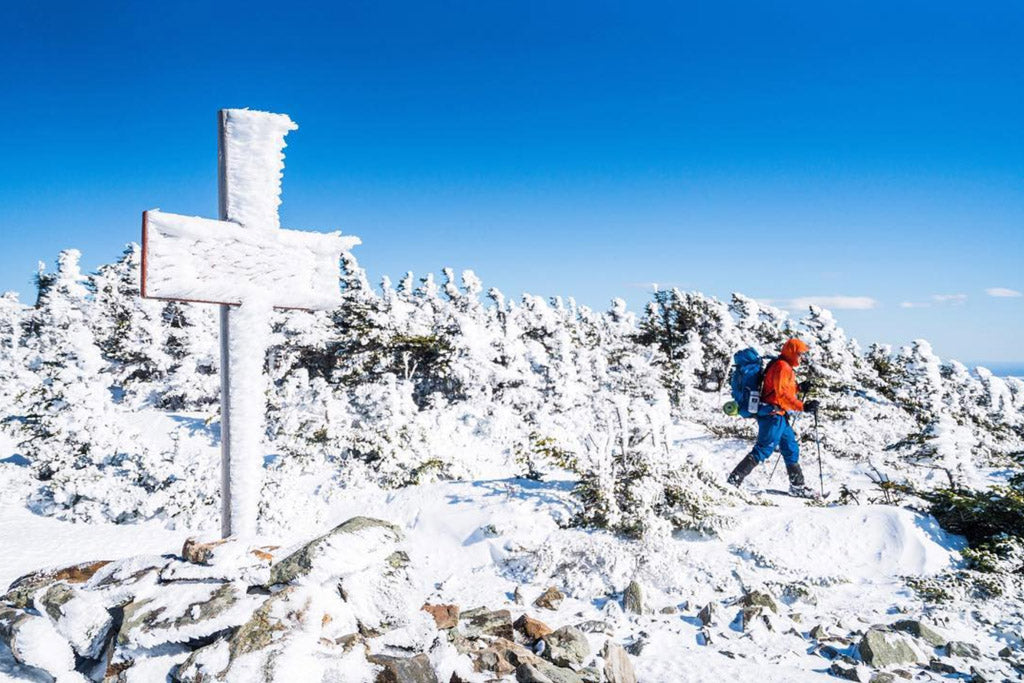 Backpacker hiking through snow covered forest past an erect cross and rock pile marking location