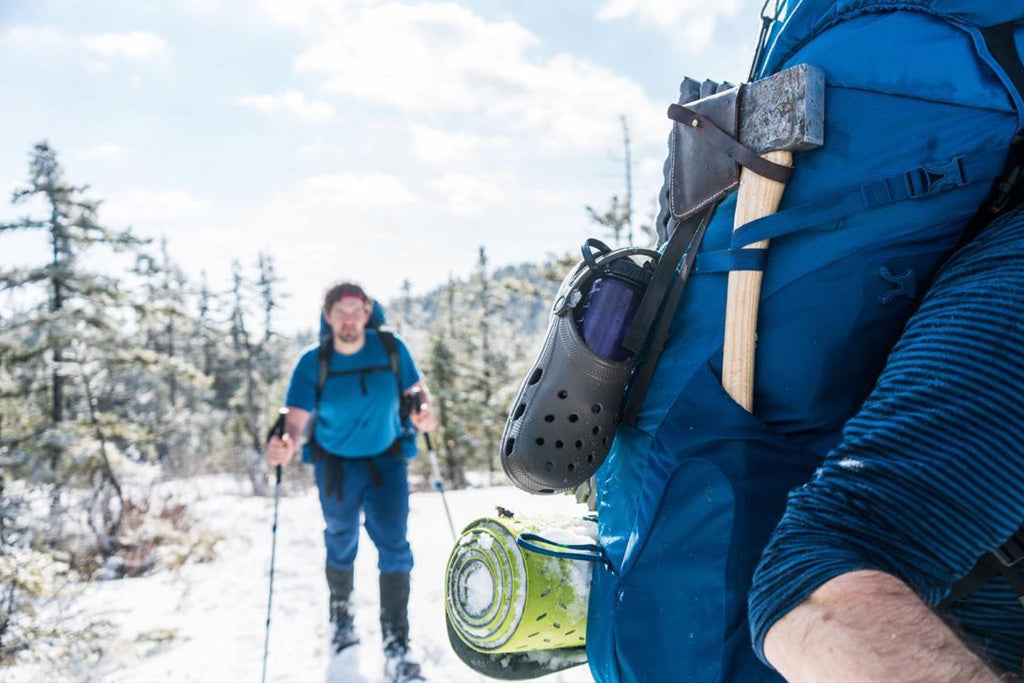 Close up of the side of a backpacker showing gear attached to pack