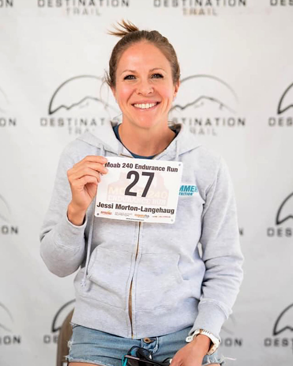 Jessi Morton-Langehaug holding bib #27 in Moab 240 pre-race picture