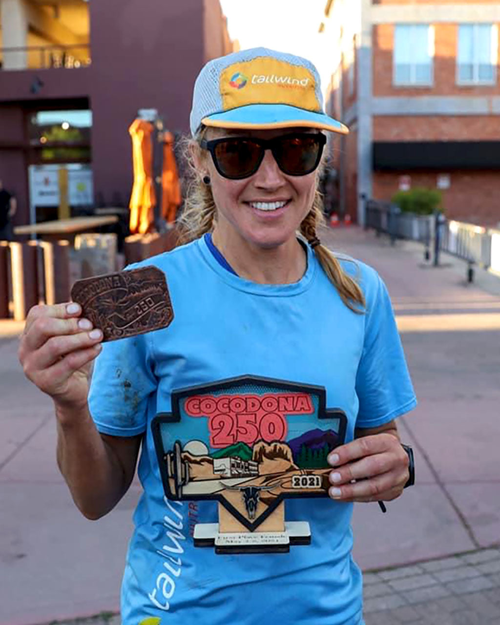 Maggie Guterl holding buckle and first place trophy for Aravaipa Cocodona 250 Ultramarathon