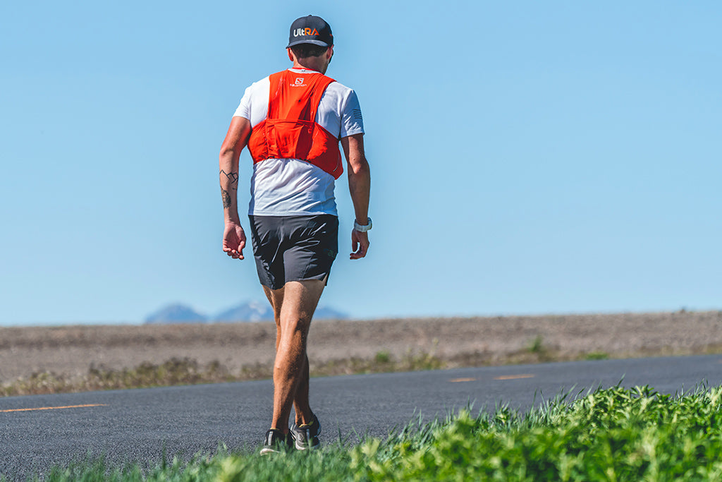 Endurance athlete Michael Mcknight wearing solomon vest and Kogalla Ultra hat running on long Cache Valley incline road.