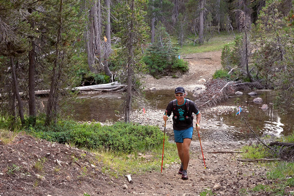Michael Mcknight crossing a stream near Wright's Lake, Tahoe.