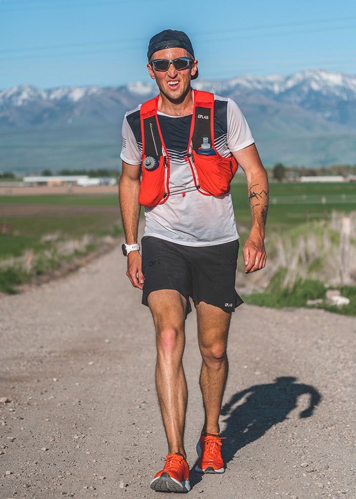 Runner Michael Mcknight wearing his trademark sunglasses on country road with Bear River mountain range in background.