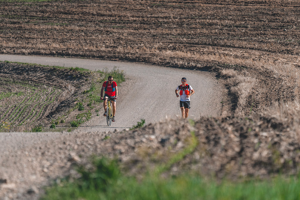 Runner Michael McKnight running through farmland with pacer on bicycle.