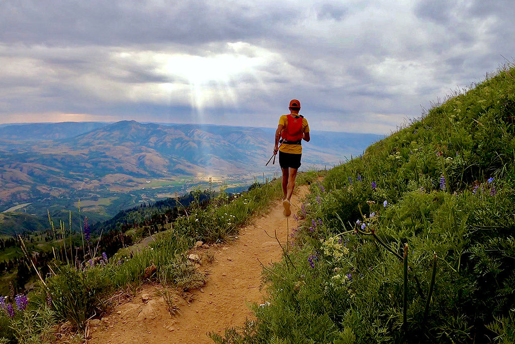 Trail runner with beautiful rays of sun coming through the cloud. Mike McKnight on Ben Lomond Trail overlooking Eden, Utah.
