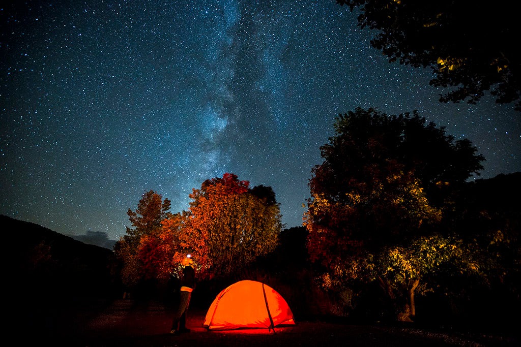 Night sky showing Milky Way galaxy with glowing red tent