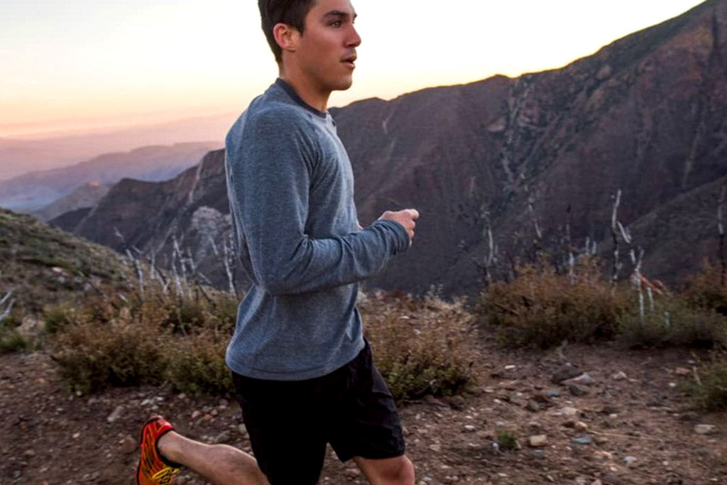 male trail runner on trail overlooking mountain peaks