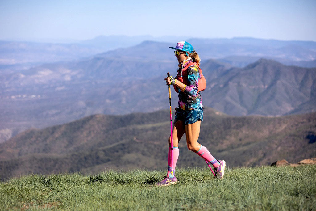 Trail runner Shelby Farrell running on trail overlooking scenic mountains.