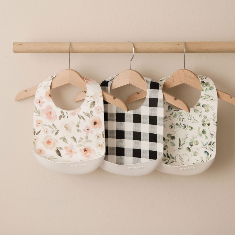 Lifestyle product photo of silicone rubber bibs. Leopard, floral and foliage prints in beige, blush and green