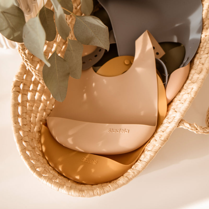 Lifestyle product photo of silicone rubber bibs. Floral, foliage and leopard prints in beige, blush pink and green
