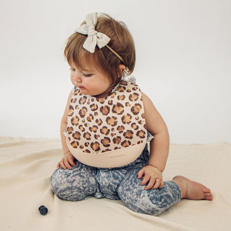 Set of 2 silicone baby bibs, sand beige and warm taupe with leopard design on lifestyle photo, Lea