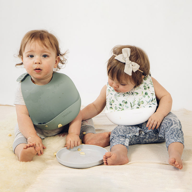 Set of 2 silicone baby bibs, sea green and white with leaves botanical design on lifestyle photo, Oliver