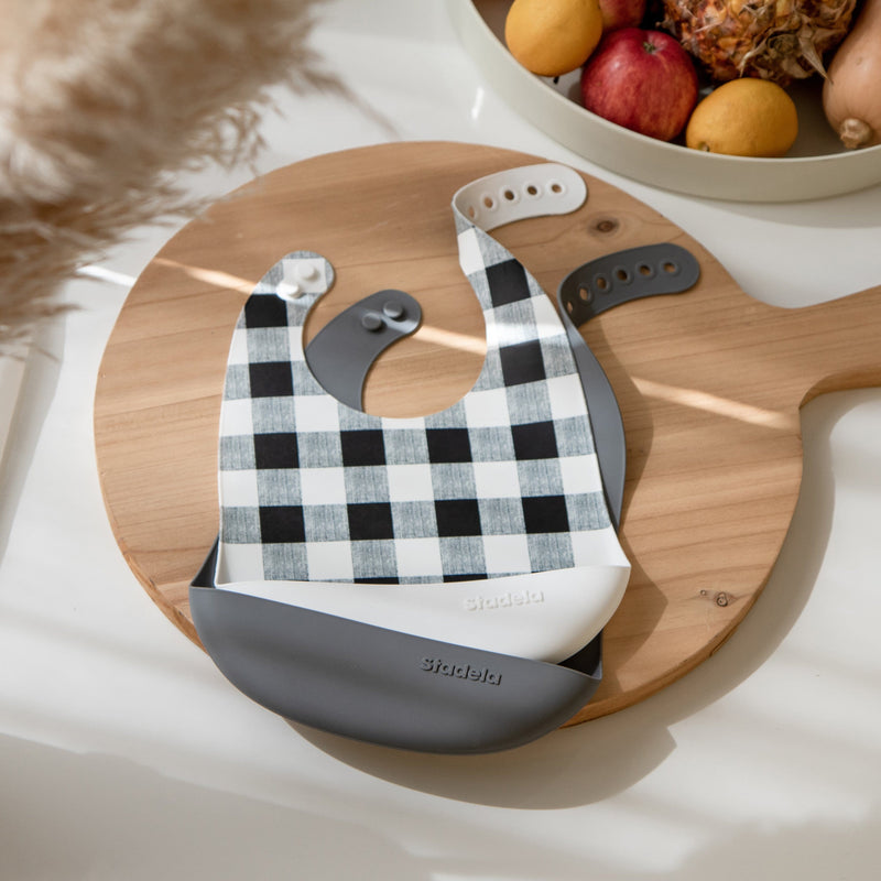 Set of 2 silicone baby bibs, cool gray and white with buffalo plaid design on lifestyle photo, Riley