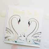 beautifully illustrated card with two parent swans and baby duckling, to congratulate parents to be, congratulate on pregnancy news.